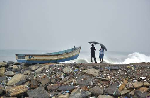 India Tv - Two men hold umbrellas to protect themselves from the rain as they stand next to a fishing boat on the Arabian Sea coast in Thiruvananthapuram, Kerala.