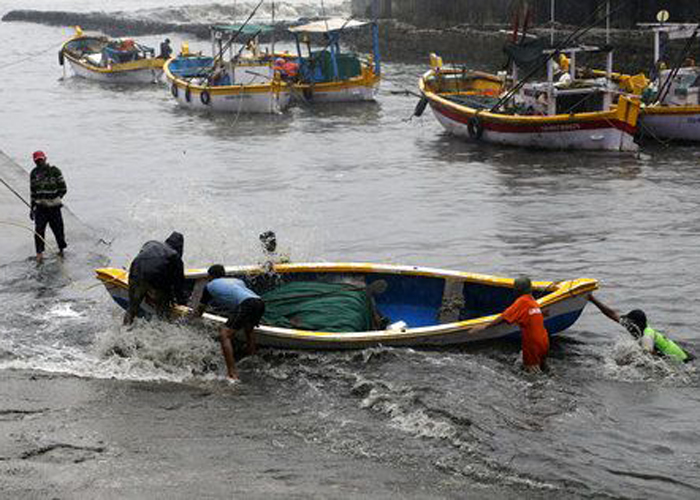 India Tv - Fishermen pull their boat during high tide in the Arabian Sea in Mumbai.