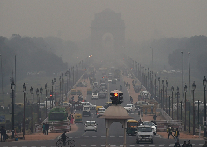 Vehicles ply at Rajpath as a thick smog engulfs India Gate