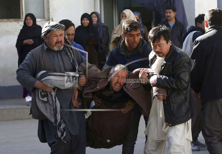 A distraught man is carried following a suicide attack in