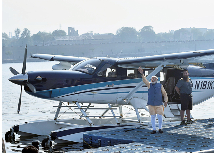 PM Narendra Modi waves to the crowd as he boards a seaplane