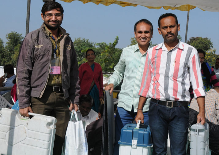 India Tv - Polling officials carry Electronic Voting Machines (EVMs) and other necessary inputs ahead of the second phase of Gujarat Assembly election at a distribution centre in Gandhinagar