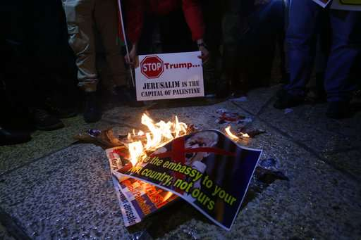 India Tv - Palestinian burn a poster of the US President Donald Trump during a protest in Bethlehem, West Bank.
