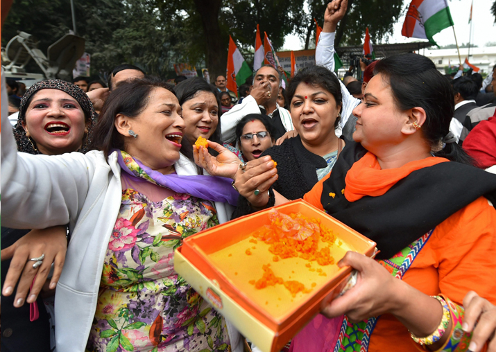 India Tv - Congress party workers distribute sweets as they celebrate after Rahul Gandhi was declared elected as the party president, outside the party headquarters, in New Delhi on Monday
