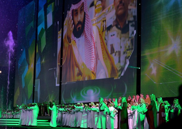 FILE - Saudi men perform under a giant screen showing an