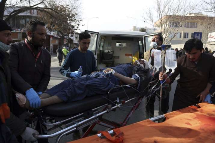 An injured man is moved on a stretcher outside a hospital
