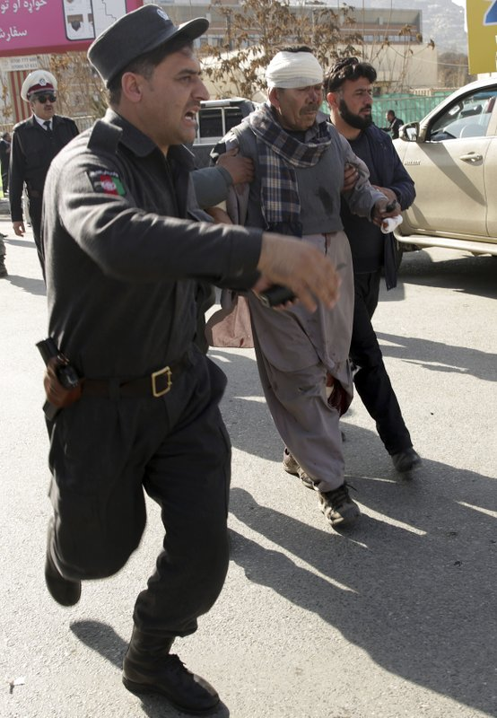 India Tv - A wounded man is assisted at the site of a deadly suicide attack in the center of Kabul, Afghanistan