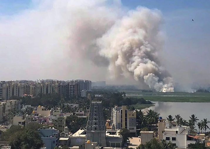 Smoke billows from a fire in middle of the wetlands of the