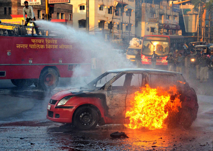India Tv - A firefighter tries to douse flames after Karni Sena activists torched a car during a demonstration against the release of the controversial film 'Padmaavat' in Bhopal on Wednesday