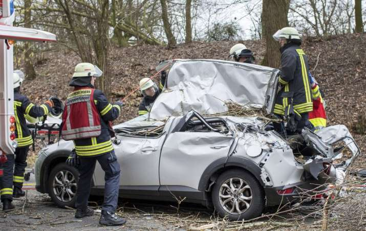 India Tv - Rescue workers are busy at the site where a car was hit by a falling tree during a storm in Moers, western Germany, Thursday, Jan. 18, 2018. The driver was seriously injured in the accident.
