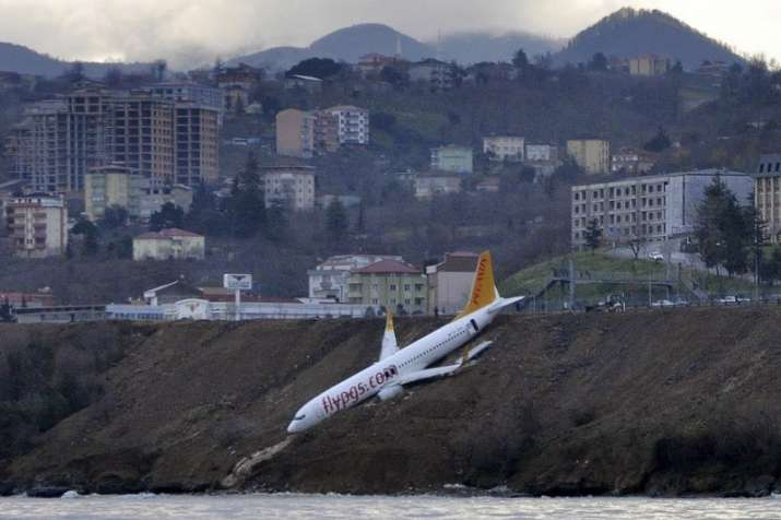 Plane dangles off cliff after skidding off runway in