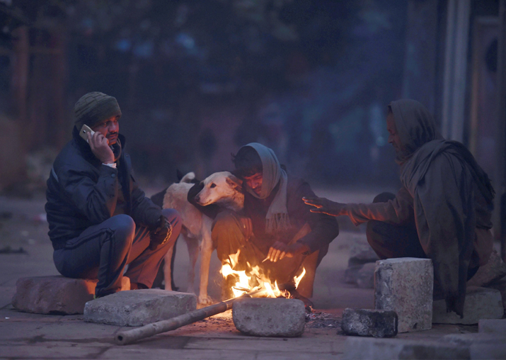 People sitting around a bonfire to warm themselves during a