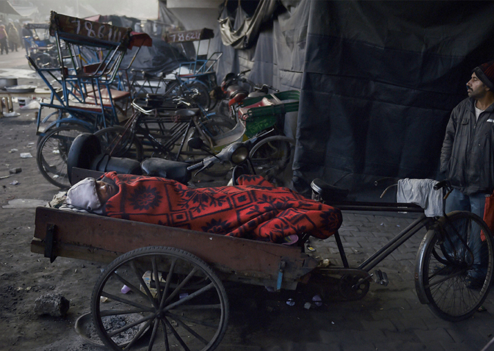 India Tv - A man wrapped in a blanket sleeps on a rickshaw during a cold winter morning in Delhi on Monday