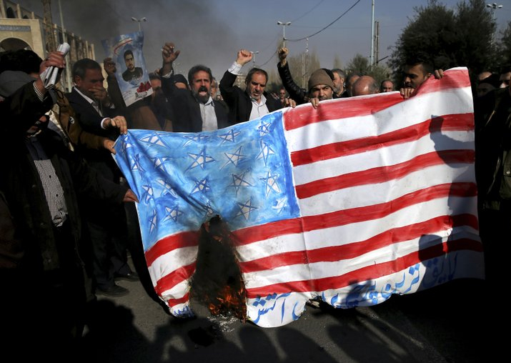 Iranian worshippers chant slogans while they burn a