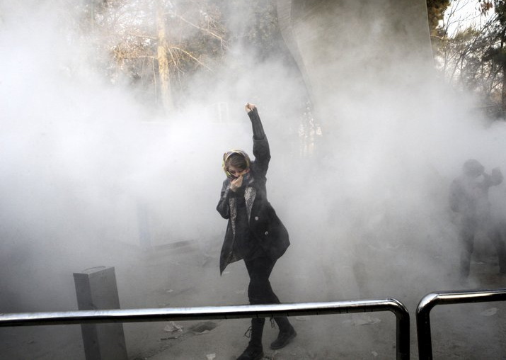 India Tv - A university student attends a protest inside Tehran University while a smoke grenade is thrown by anti-riot Iranian police