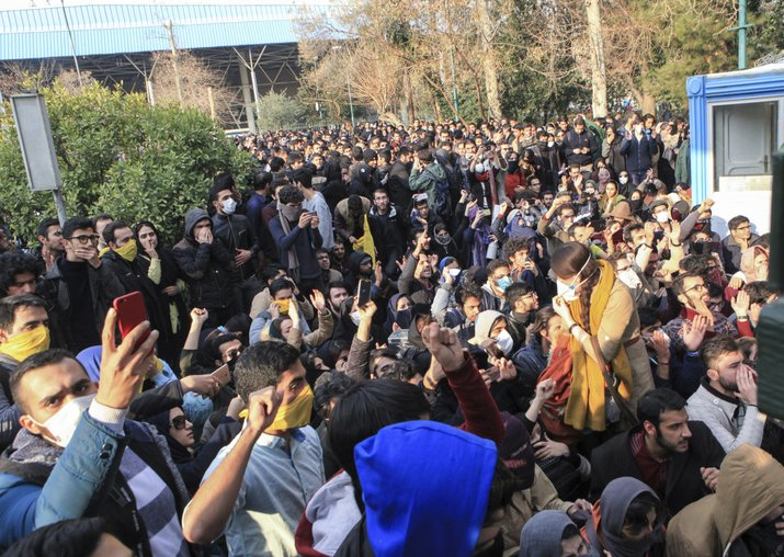 India Tv - University students attend a protest inside Tehran University while anti-riot Iranian police prevent them to join other protestors, in Tehran