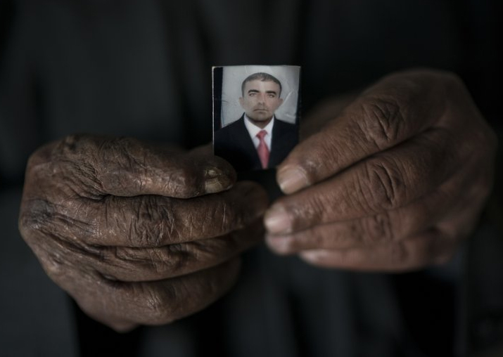 Ghanim Ahmed holds the photo of his son Ghazwan Ahmed, who