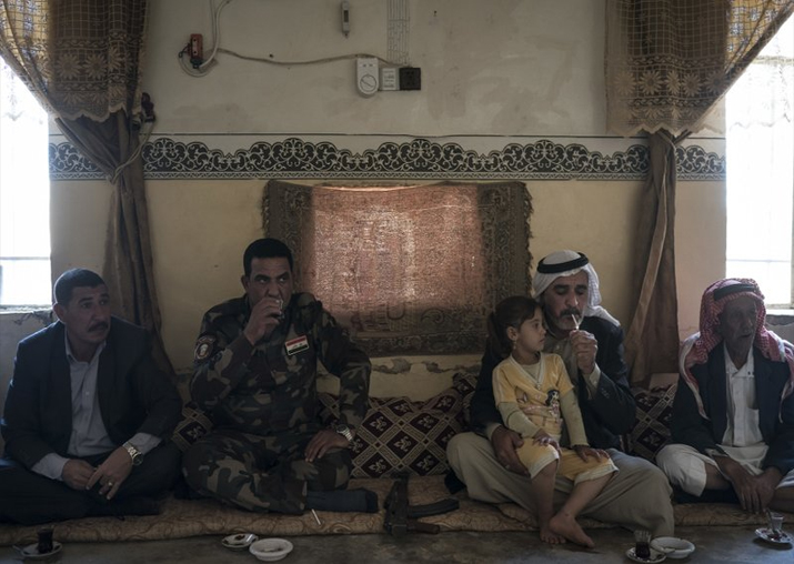 India Tv - In this Nov. 12, 2017 photo, a local fighter and residents gather at the mayor's home in the Bijwaniya village, south of Mosul