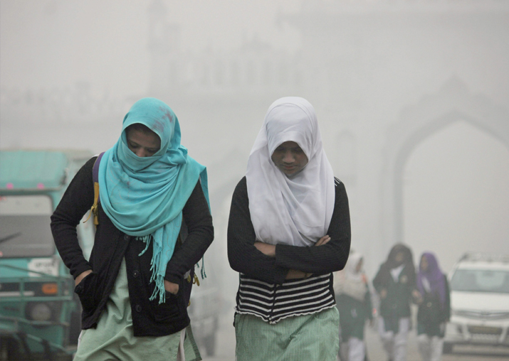 India Tv - Children going to school amidst heavy fog on a cold morning in Lucknow on Tuesday