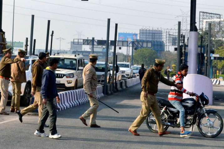 India Tv - Policemen detain a biker for damaging DND toll near Noida toll in protest against