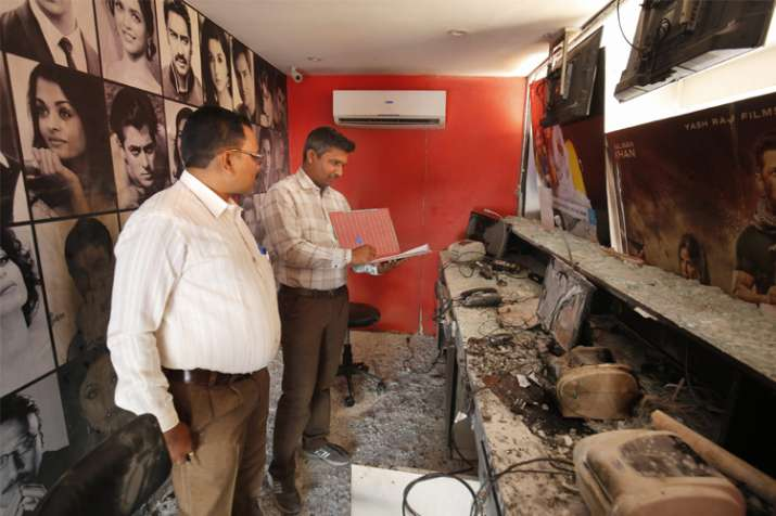 """India Tv - Forensic experts examine the ticket counter of the cinema hall after it was vandalised in protest against the release of the film """"Padmaavat"""" in Ahmedabad on Sunday."""