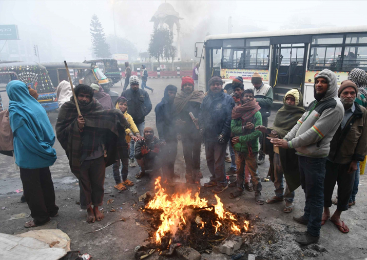 India Tv - People warm themselves around a fire on a cold day in Patna
