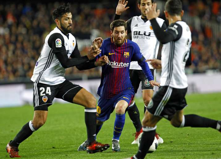 India Tv - Lionel Messi dribbles past the Valencia defence.