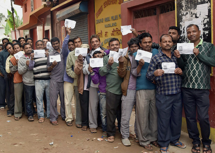Voters wait in a long queue to cast their votes for