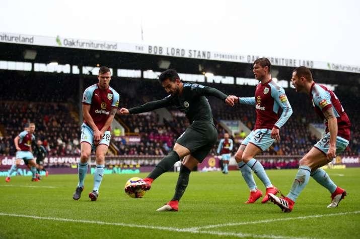 India Tv - Burnley players tackle City's Ilkay Gundogan.