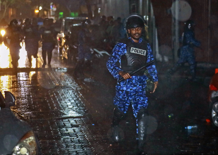 A Maldives policeman charges with baton towards protesters