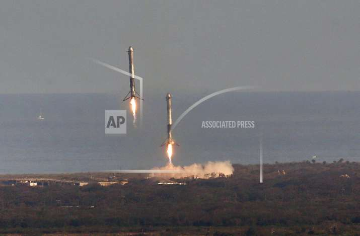 India Tv - Two Falcon boosters come back to land at Cape Canaveral after SpaceX's Falcon Heavy rocket lifted off from launch Pad 39A Tuesday, February 6, 2018, for the maiden demonstration test flight at the Kennedy Space Center.