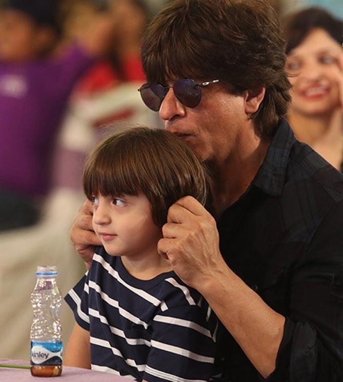 India Tv - SRK clicked having a cute moment with youngest son ABram.