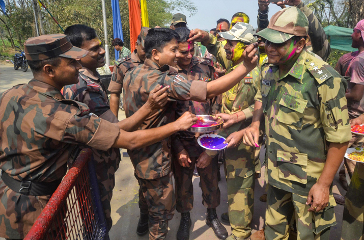 India Tv - BSF soldiers smear 'gulal' on Border Guard of Bangladesh (BGB) soldiers during 'Holi' celebration at India-Bangladesh Akhaura border near Agartala on Friday.