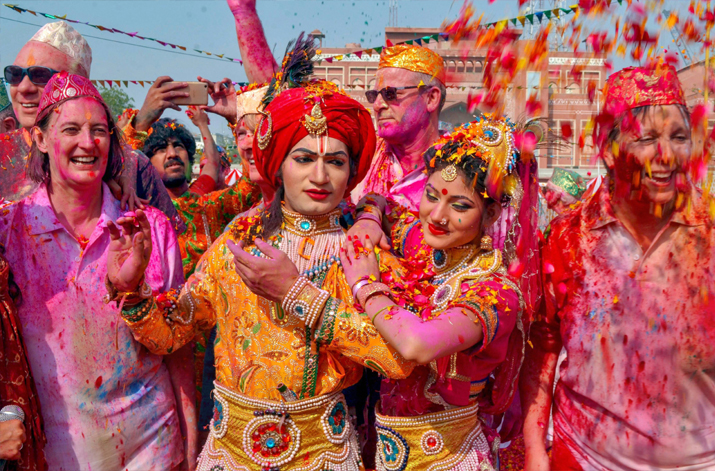 India Tv - Artists dressed as Lord Krishna and Radha pose for a photograph as foreign tourists throw flower petals and coloured powder during Holi celebration at Kalakriti in Agra on Friday.