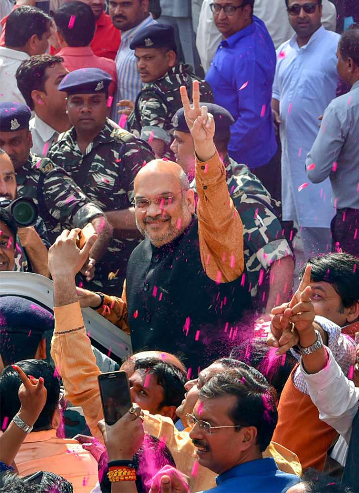 India Tv - Amit Shah flashes victory sign as he is accorded welcome by party workers as they celebrate outside party headquarters after North-East states Assembly election results, in New Delhi on Saturday.