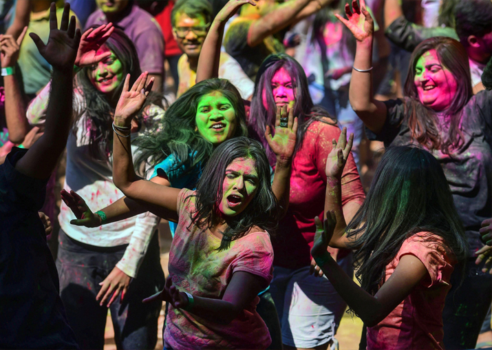 India Tv - Revelers with their face smeared with 'gulal' joyfully dance during the 'Holi' festival celebration, in Bengaluru on Friday.