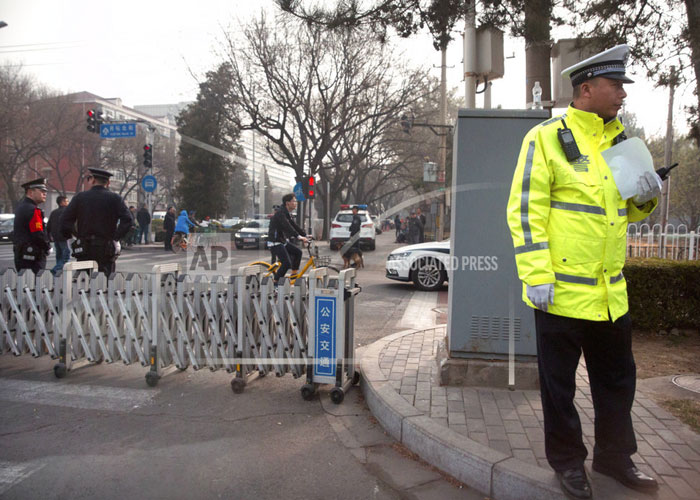 Chinese policemen stand guard at a road barricade in front
