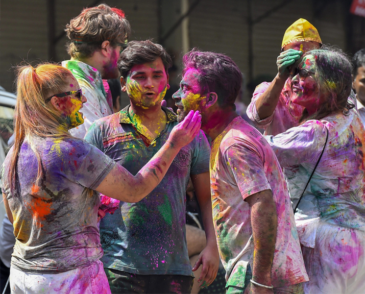 India Tv - Foreigners and locals smear 'gulal' on each other as they celebrate Holi festival at Paharganj area in New Delhi on Friday.