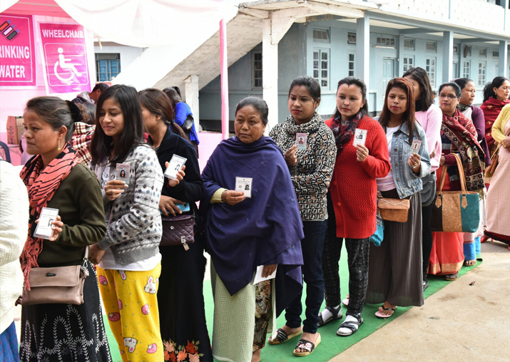 India Tv - Voters wait in a queue to cast their votes during Meghalaya Assembly elections in Shillong on Feb 27