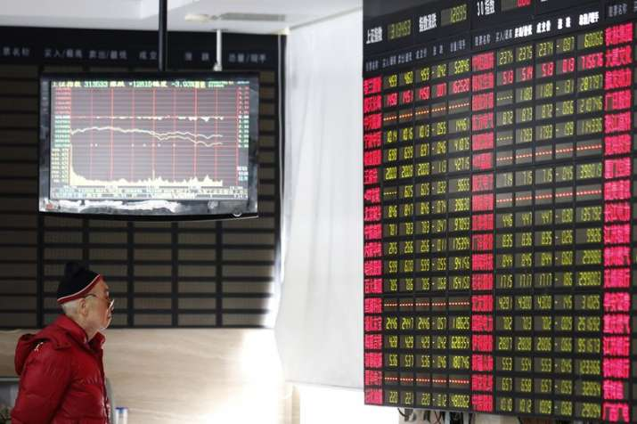 An investor looks at a stock price display screen at a