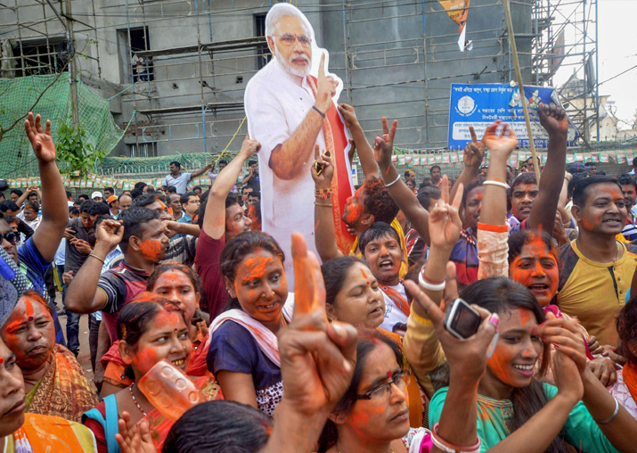 BJP supporters hold up a placard of Prime Minister Narendra