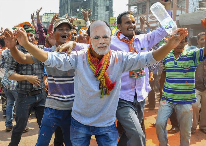 BJP supporters wear a mask of Prime Minister Narendra Modi