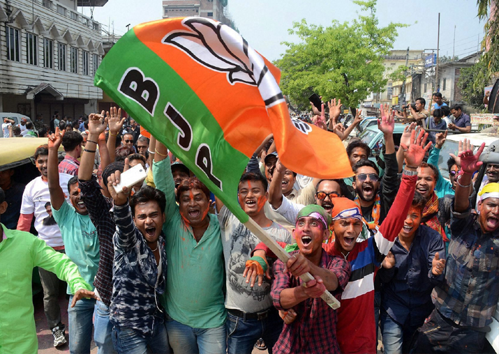 India Tv - BJP supporters wave party flag to celebrate BJP's win, which brought down 25 years of CPI-M government rule, after Tripura Assembly election results were announced in Agartala on Saturday.