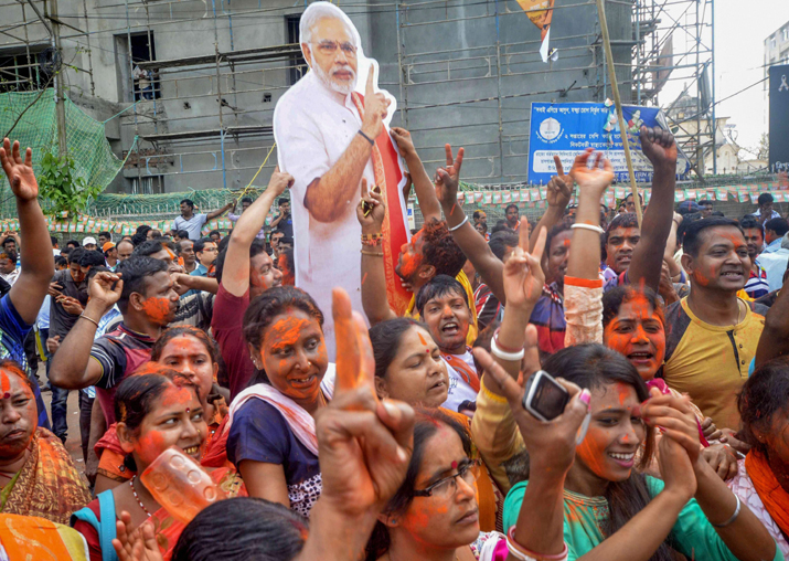 India Tv - BJP supporters hold up a placard of Prime Minister Narendra Modi after party's victory in Tripura Assembly elections results in Agartala on Saturday.