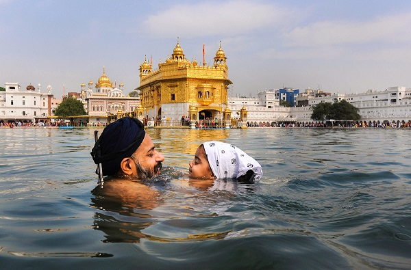 India Tv - A Sikh devotee, along with his child, takes holy dip in the Sarovar of Harmandir Sahib (Golden Temple) on the occasion of Baisakhi festival.