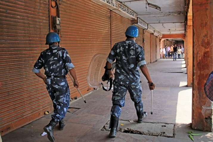 Jaipur: Rapid Action Force personnel walk past closed shops