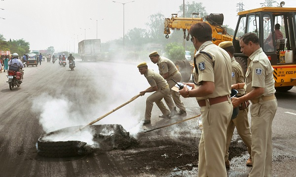 India Tv - Police personnel extinguish a burning tyre to clear a road during 'Bharat Bandh' against the alleged 'dilution' of Scheduled Castes and Scheduled Tribes act, in New Delhi, on Monday