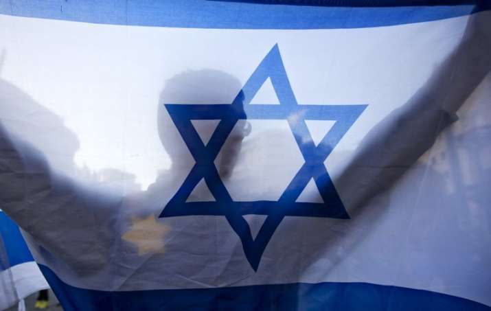 A right-wing Israeli holds a flag and wears a Star of David