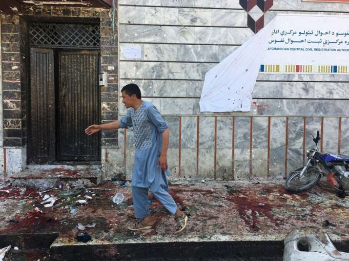 An Afghan man walks outside a voter registration center, which was attacked by a suicide bomber in K