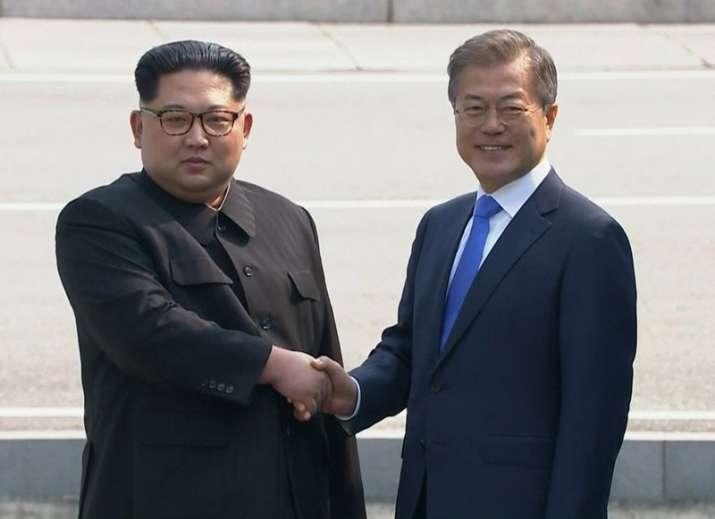 North Korean leader Kim Jong Un, left, shakes hands with